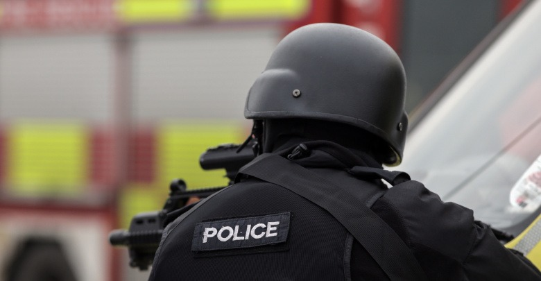 Firearms Officer leaning over a vehicle bonnet
