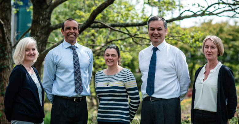 Independent Advisors stood together in front of a tree