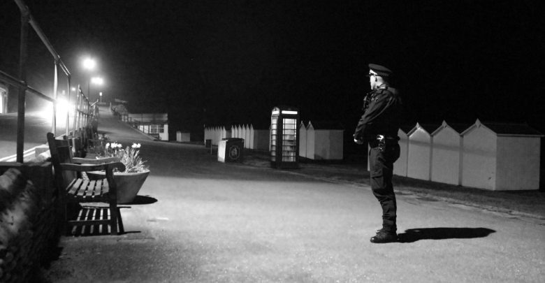 Constable standing on his own at night
