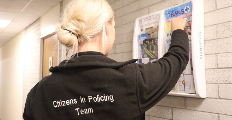Volunteer in the Police Station putting up a poster