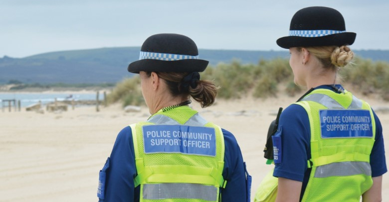 Two female Dorset PCSOs on patrol by the sea